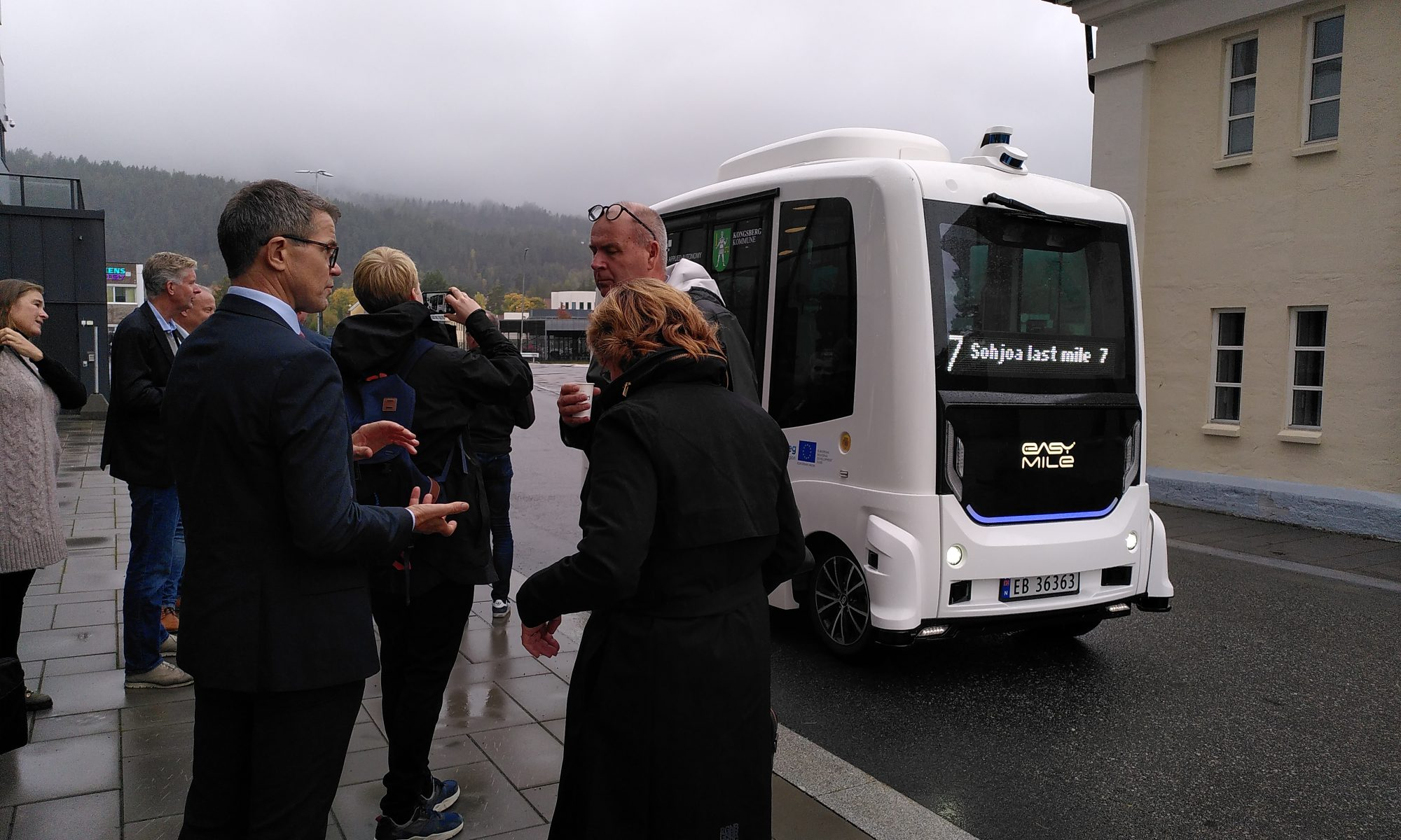A group of people standing outside in the left, background grey and rainy skies and a silhouette of a hill, a robot bus on the road, a house on the right.
